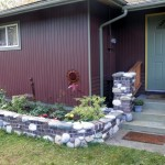 Clinker brick and stone flower bed and column